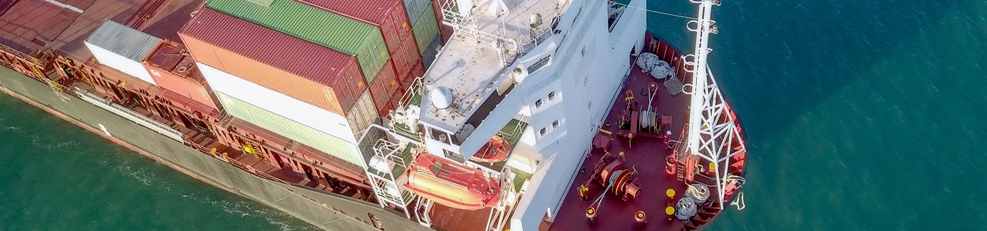 Large Cargo and RoRo (Roll On-Off) ship at sea, loaded with a small amount of shipping containers